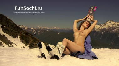 Nude woman sunbathes in mountains with ski