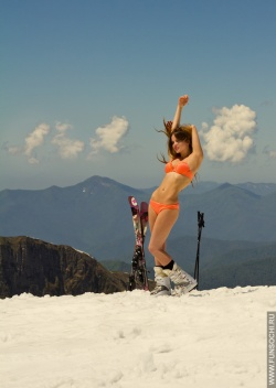 Smiling girl in bathing suit at mountains with ski