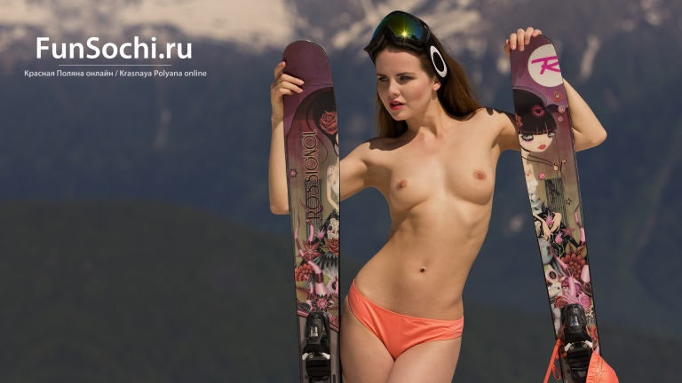 Naked woman in mountains with ski